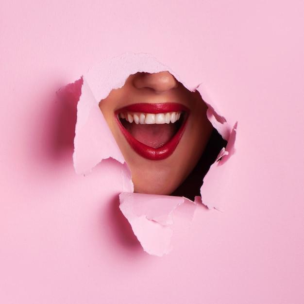 Labbra rosse luminose attraverso sfondo di carta rosa strappato. ragazza sorpresa, emozioni. Foto Premium