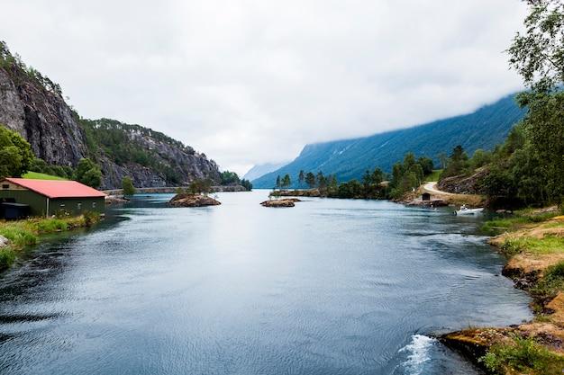 Lago blu idilliaco con la montagna nebbiosa Foto Gratuite