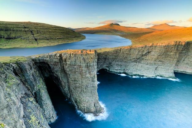 Lago leitisvatn e tralanipan, roccia schiava al tramonto. isola di vagar, isole faroe. danimarca Foto Premium