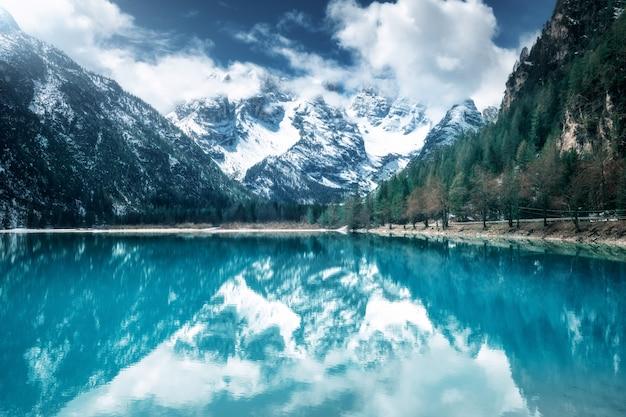 Lago mountain con la riflessione perfetta al giorno soleggiato in autunno. dolomiti, italia. bellissimo paesaggio con acqua azzurrata, alberi, montagne innevate in nuvole, cielo blu in autunno. Foto Premium