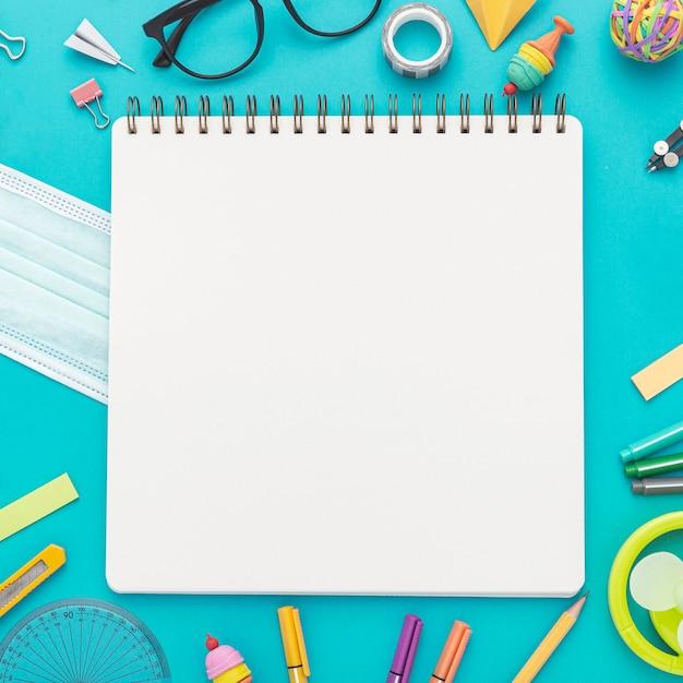 Laici piatta di ritorno a materiale scolastico con matite e quaderno Foto Gratuite