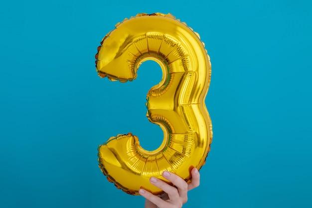 Lamina d'oro numero 3 palloncino a tre feste Foto Premium