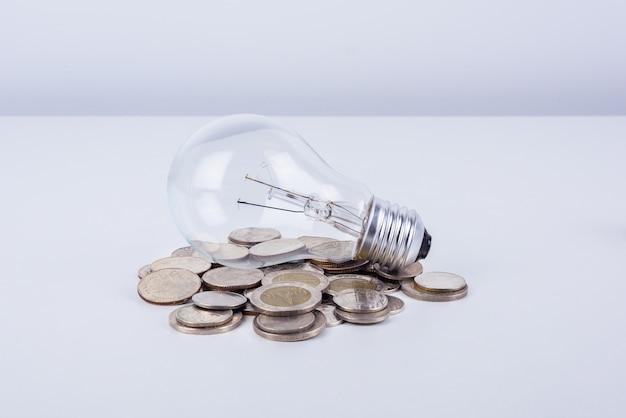 Lampada a incandescenza e soldi di energia su fondo bianco
