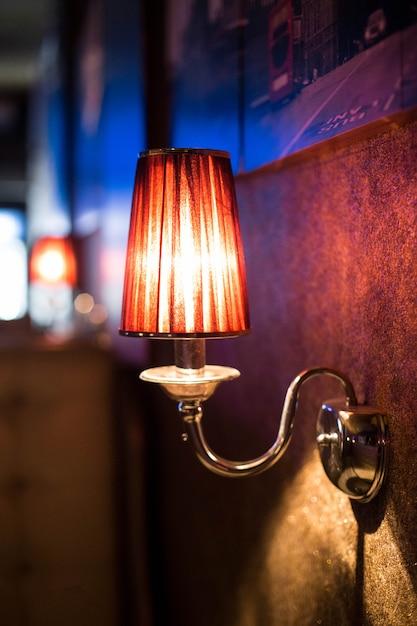 Lampada da parete in un locale notturno. bella luce soffusa dalla lampada Foto Premium