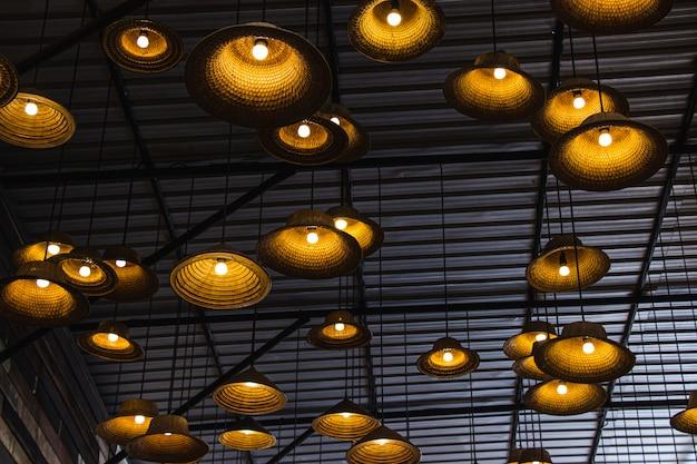 Lampada fabbricata da un cappello fatto di materiali locali di bambù all'interno del ristorante al mercato galleggiante di amphawa. Foto Premium