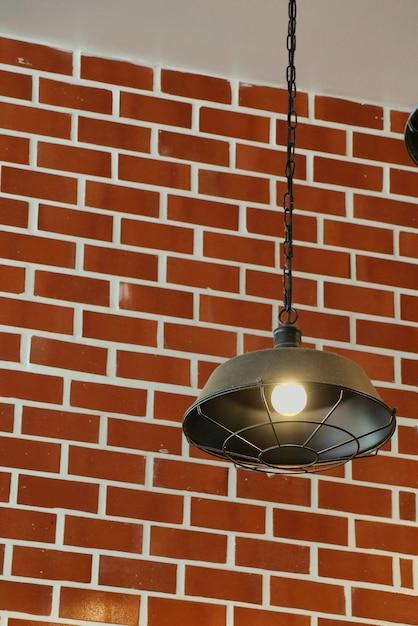 Lampada vintage appesa al soffitto con luce sul muro di mattoni. Foto Premium