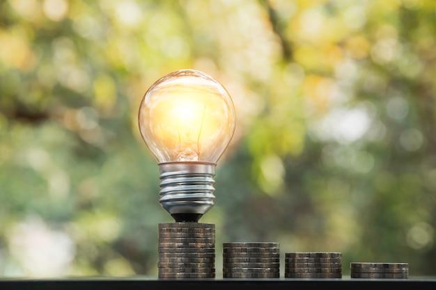 Lampadina a risparmio energetico con pile di monete per il risparmio, finanziario e contabile Foto Premium