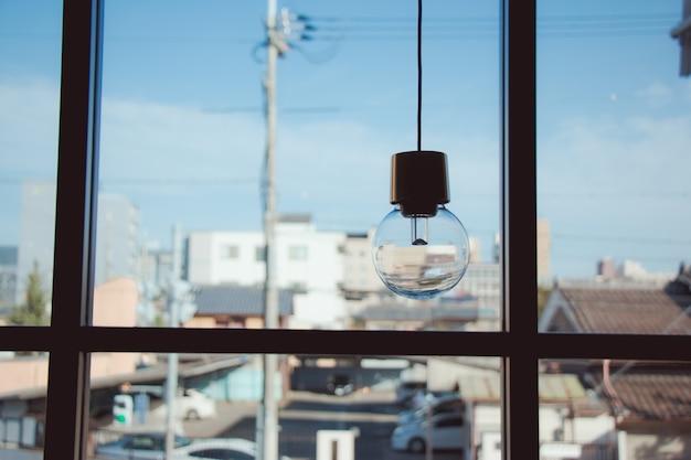 Lampadina a sospensione vicino alla finestra di vetro Foto Premium