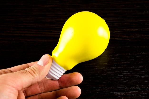 Lampadina gialla come simbolo dell'idea su uno sfondo scuro Foto Premium