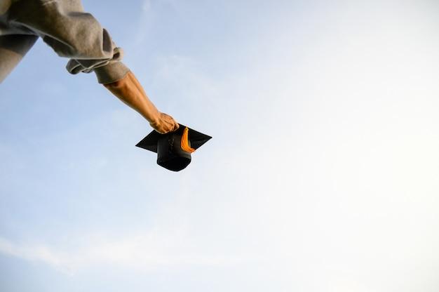 Lancia un cappello nero di laureati nel cielo. Foto Premium