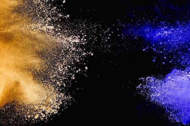 Lanciato spruzzi di particelle di polvere giallo-blu su sfondo. Foto Premium