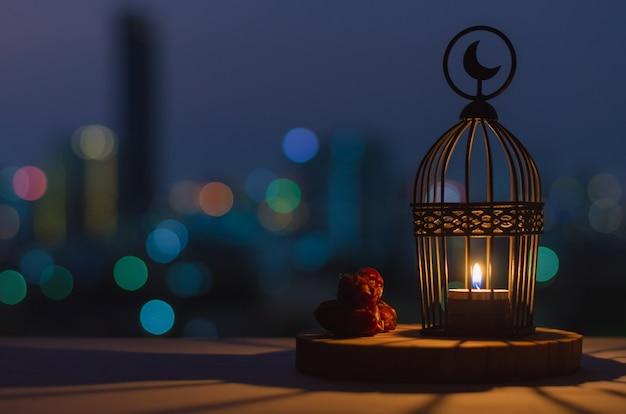 Lanterna che ha il simbolo della luna in cima e data frutta messa sul vassoio di legno con luci colorate della città bokeh per la festa musulmana del mese santo di ramadan kareem. Foto Premium