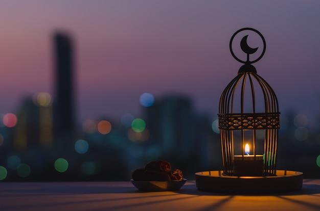 Lanterna che ha il simbolo della luna in cima e un piccolo piatto di datteri con il cielo al crepuscolo e il bokeh della città sullo sfondo di luce per la festa musulmana del mese santo di ramadan kareem. Foto Premium