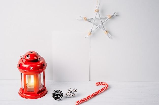 Lanterna rossa con una candela, pigne, stelle e vuoto foglio bianco su uno sfondo bianco. decorazione natalizia Foto Premium