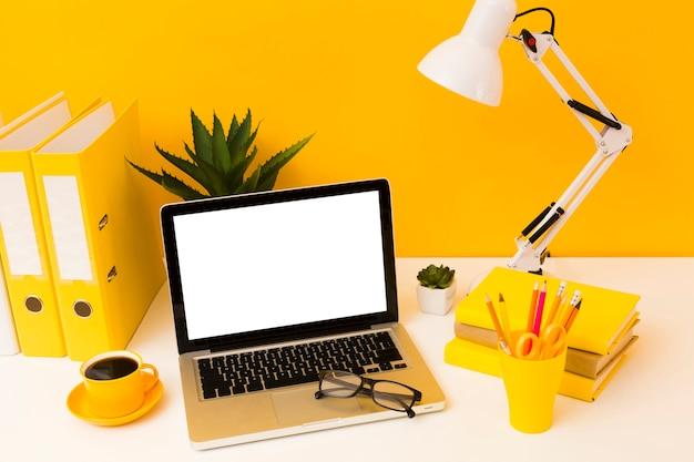 Laptop accanto a cartoleria gialla Foto Gratuite