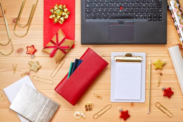 Laptop, carte di credito, borsa e decorazioni natalizie. shopping natalizio online, acquisto di regali Foto Premium