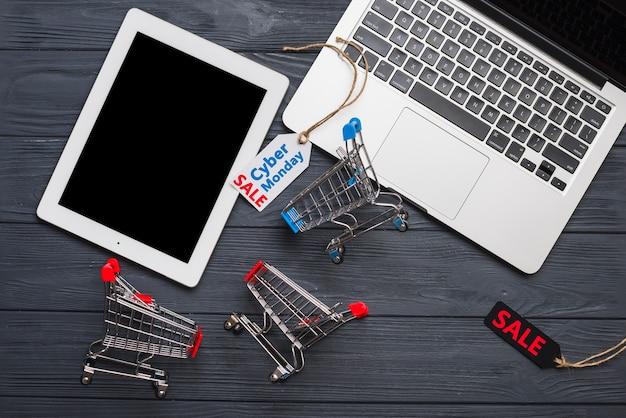 Laptop vicino a tag, tablet e carrelli del supermercato Foto Gratuite
