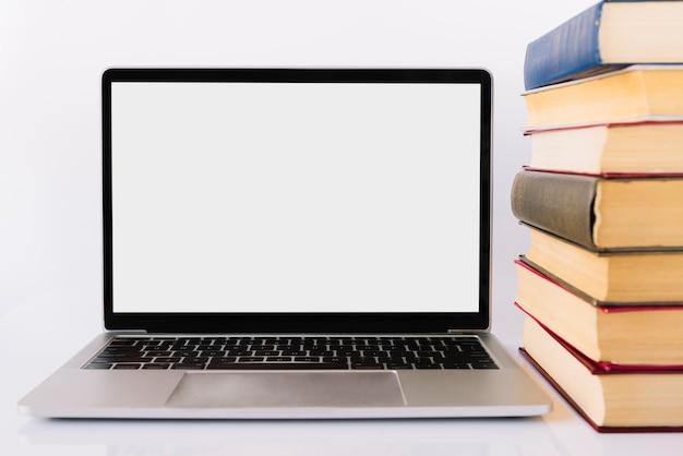 Laptot accanto al mucchio del libro Foto Gratuite