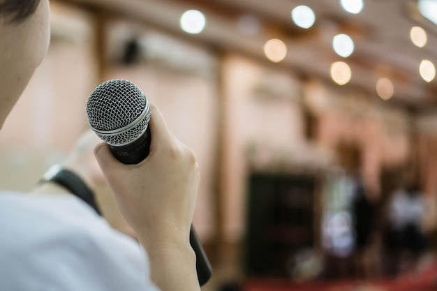 Lato posteriore del discorso di imprenditrice intelligente e parlando con il microfono Foto Premium