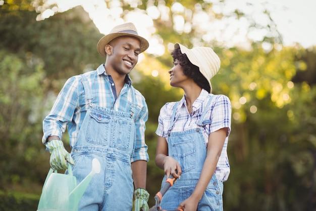 Latta di innaffiatura sorridente della tenuta delle coppie e cesoie di giardinaggio nel giardino Foto Premium
