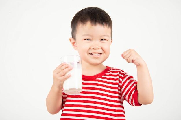Latte alimentare del piccolo ragazzo asiatico da vetro con il fronte felice Foto Premium
