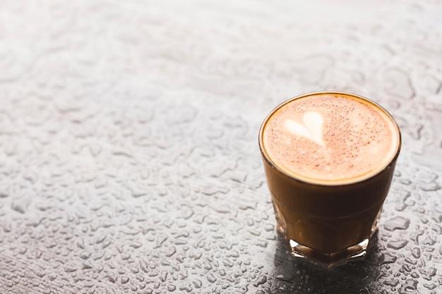 Latte caldo con forma di cuore in vetro sulla superficie di goccia d'acqua Foto Gratuite