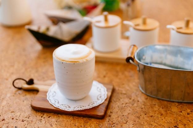 Latte caldo servito in tazza di ceramica sul piatto di legno. liscio schiuma bianca e marrone. Foto Premium