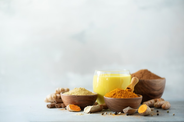 Latte curcuma vegano sano o latte dorato, radice di curcuma, polvere di zenzero, pepe nero su sfondo grigio cemento. Foto Premium