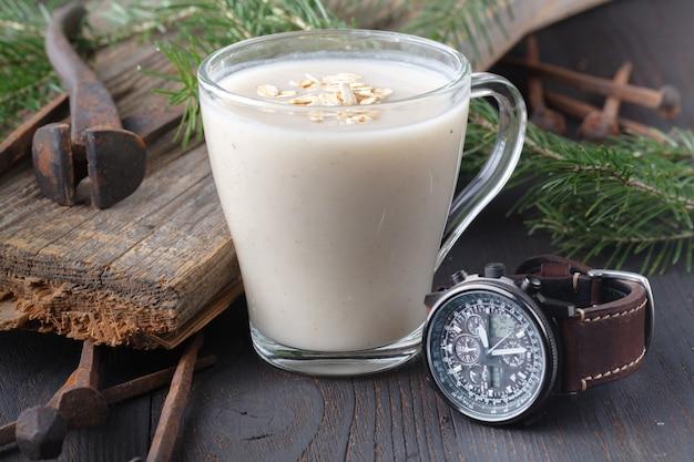 Latte d'avena fatto in casa, orologio da polso e ramo di ramoscello Foto Premium