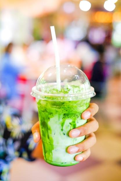 Latte del ghiaccio del tè verde di matcha in un vetro a disposizione Foto Premium