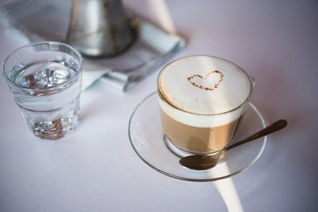Latte della tazza di caffè del primo piano con bicchiere d'acqua Foto Gratuite