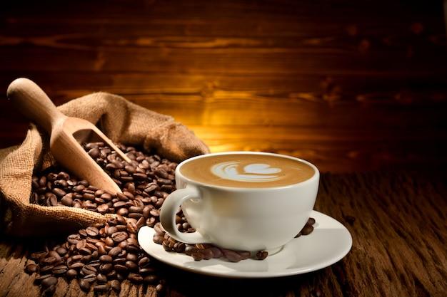 Latte della tazza di caffè e chicchi di caffè su vecchio fondo di legno Foto Premium