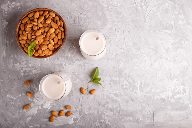 Latte di mandorle biologico non da latte in vetro e piatto di legno con noci di mandorle su un cemento grigio. Foto Premium