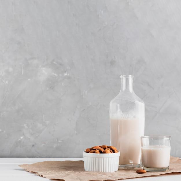 Latte di mandorle in vetro e bottiglia con mandorle Foto Gratuite