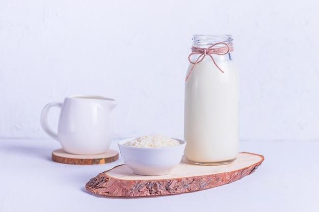 Latte di riso vegano in una bottiglia di vetro e riso in un piatto bianco su un supporto in legno su uno sfondo bianco Foto Premium
