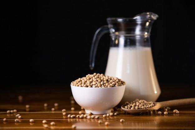 Latte di soia caldo e soia sul fondo di legno della tavola Foto Premium