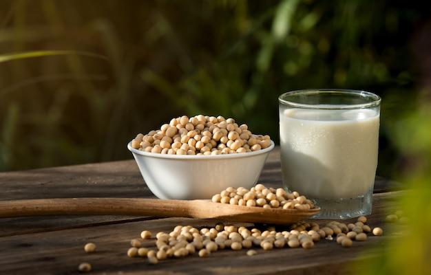 Latte di soia fresco e soia sulla tavola di legno Foto Premium