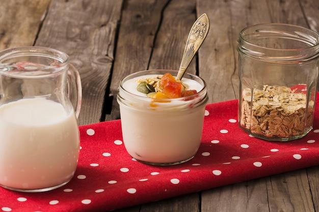 Latte, yogurt e avena secca nel barattolo di vetro sul tovagliolo rosso sopra il tavolo di legno Foto Gratuite