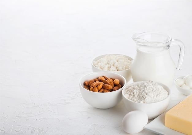 Latticini freschi sulla tavola bianca. vaso di vetro di latte, ciotola di ricotta e farina da forno e noci di mandorle. uova e formaggio Foto Premium