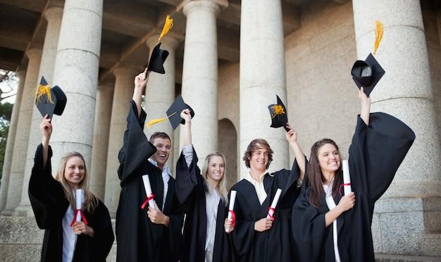 Laureati sorridenti che tengono i loro cappelli davanti all'università Foto Premium