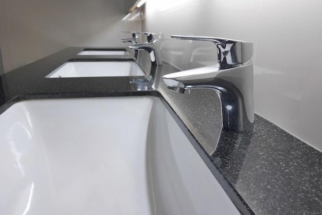 Lavabi bianchi e rubinetto sul bancone in granito in bagno Foto Premium