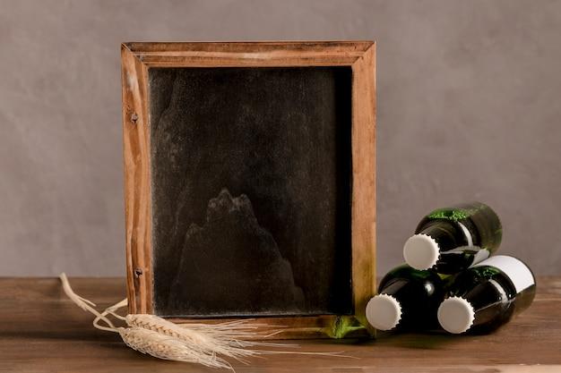Lavagna accanto a tre bottiglie di birra sul tavolo di legno Foto Gratuite