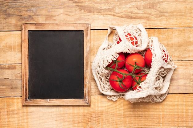 Lavagna accanto al sacco di pomodori Foto Gratuite