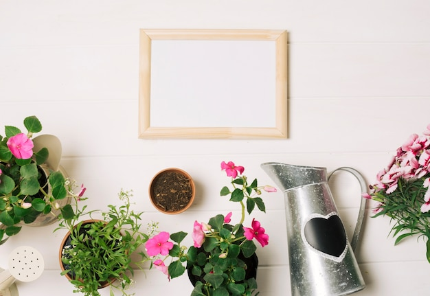 Lavagna bianca con fiori sul tavolo bianco Foto Gratuite