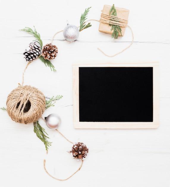 Lavagna circondata da decorazioni natalizie Foto Gratuite