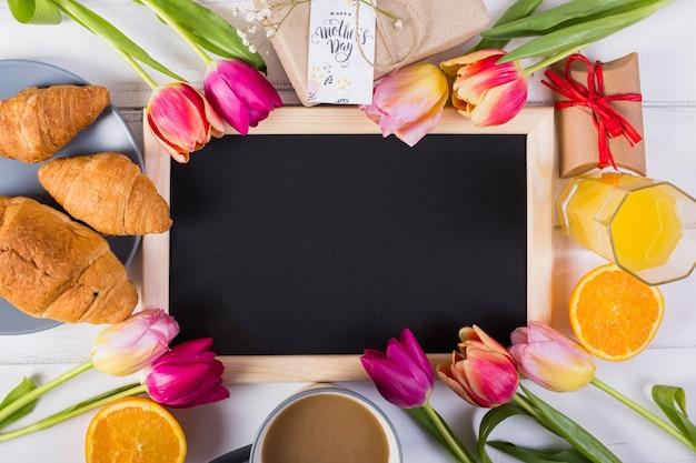 Lavagna con cornice intorno a tulipani e colazione Foto Gratuite