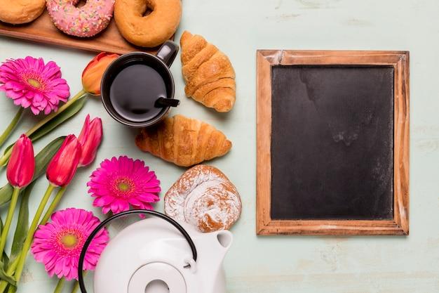 Lavagna cornice vicino a tea-party e pasticceria Foto Gratuite
