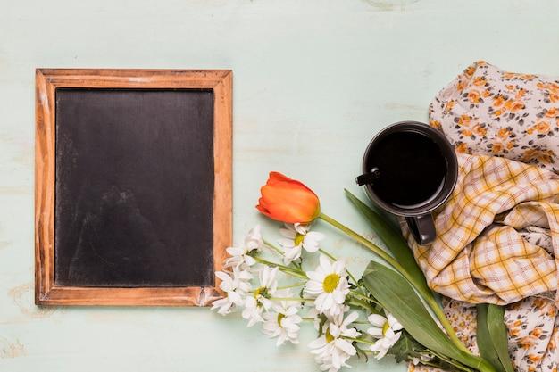 Lavagna decorata con fiori e tazza Foto Gratuite