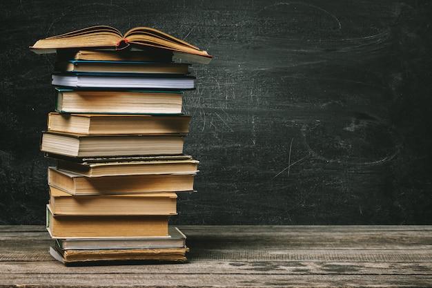 Lavagna della scuola con una pila di libri Foto Premium