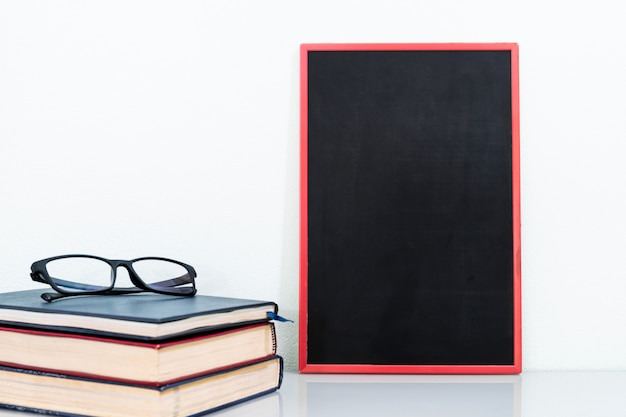 Lavagna mock up frame e libri antichi con gli occhiali Foto Premium